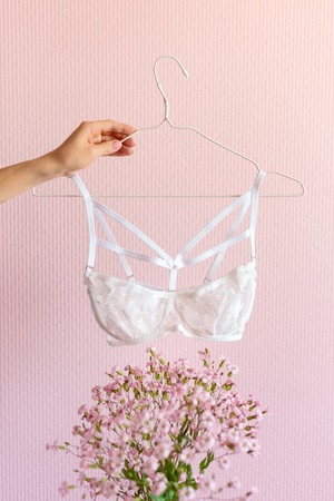 Woman hand holding bra on pink background with flowers. Lingerie in hands, fashion and sale concept Stock Photo