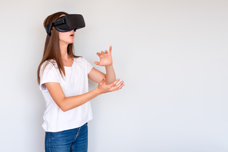 Smiling positive woman wearing virtual reality goggles headset, vr box. Connection, technology, new generation, progress concept. Girl trying to touch objects in virtual reality. Studio shot on gray. Фото со стока