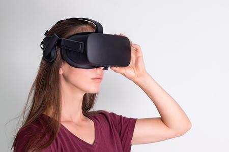 Mujer joven con casco de gafas de realidad virtual, caja vr. Conexión, tecnología, nueva generación, concepto de progreso. Chica tratando de tocar objetos en realidad virtual. Foto de estudio en gris.