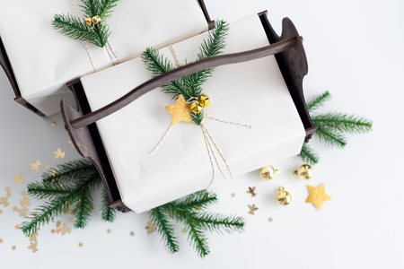 Luxury New Year gift with gold decoration and tree branches. Christmas gift in wooden basket. Christmas background with gift box. Presents for Christmastime celebration 免版税图像
