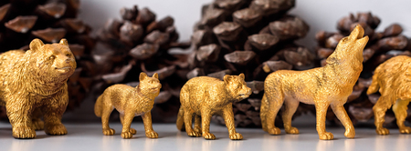 Golden Christmas decorations, marten, wolf and bear figures, models toys. Pine cones on the background. Christmastime concept. 免版税图像