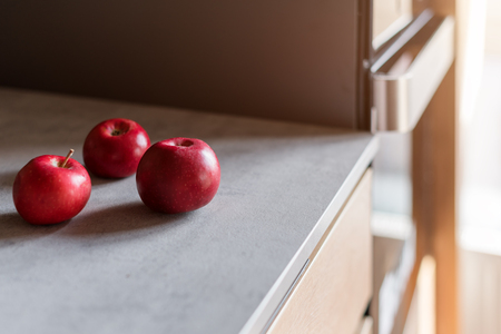Kitchen table with red apples. Modern kitchen interior, close up Imagens