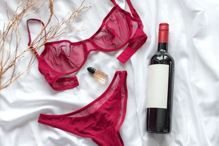 Top view fashion red lace lingerie with bootle of red wine and perfume. Set of woman essential accessory and underwear. Flat lay on white bedsheets background. Shopping and fashion concept.