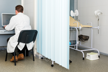 Doctor typing and using his computer in the office. Modern hospital with gynecological chair. Gynecologist waiting for the next patient.