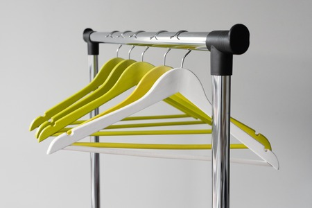 Empty clothes hangers on metal rail against grey background. Rectangular metal clothing rail with empty color wooden coat hangers. Stockfoto