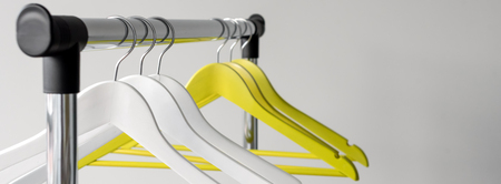 Empty clothes hangers on metal rail against grey background. Rectangular metal clothing rail with empty color wooden coat hangers. 版權商用圖片