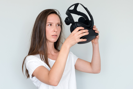 Young woman holding virtual reality goggles headset, vr box. Connection, technology, new generation, progress concept. Studio shot on gray.