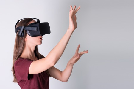 Young woman wearing virtual reality goggles headset, vr box. Connection, technology, new generation, progress concept. Girl trying to touch objects in virtual reality. Studio shot on gray Imagens