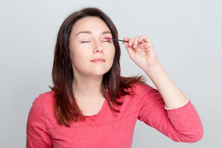 Woman doing her make up, preparing lashes, brushing eyelashes using brush tool. Cosmetic procedure of eyelash care at the stage of combing. Building, painting, laminating eyelashes