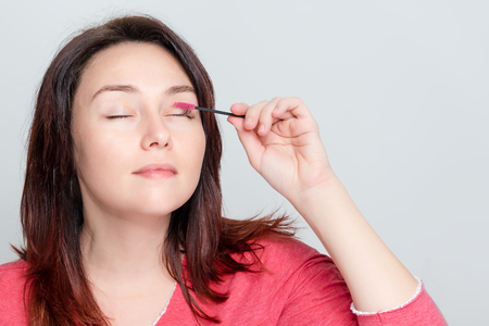 Woman doing her make up, preparing lashes, brushing eyelashes using brush tool. Cosmetic procedure of eyelash care at the stage of combing. Building, painting, laminating eyelashes. Copyspace for text Imagens