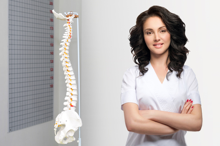 Young pretty female doctor in uniform keeping arms crossed and looking at camera. Artificial human cervical spine model in medical office. Orthopedic practice Stockfoto