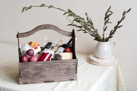 Easter cake, colored eggs, meat and bottle of red wine. Orthodox sweet bread, kulich on light background. Gifts for holiday in wooden basket with spring flowers on light natural fabric background.