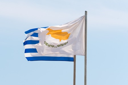 Waving Greek and Cyprian flags agaist the blue sky in strong wind Reklamní fotografie