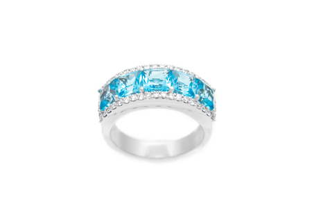Diamond ring with blue precious gems. White golden ring on white background. Fashion luxury accessories