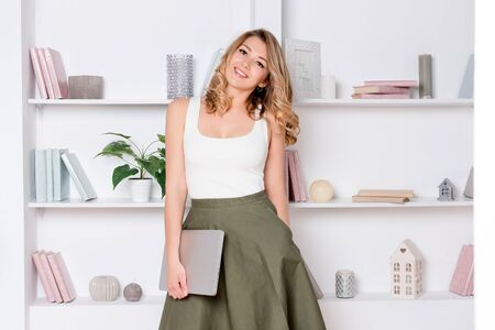 Young woman holding laptop, working on computer or student studying. Casual blogger woman with laptop, working at home, female business. Blonde business woman looking happy and smiling