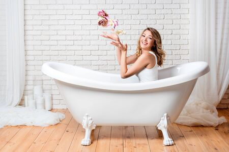 Woman in bath having fun with flowers. Beautiful young blonde woman enjoying pleasant bath, looking at camera and smiling Stok Fotoğraf