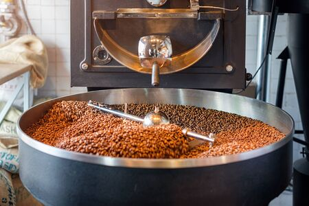Freshly roasted coffee beans from a large roaster in the cooling cylinder. Motion blur on the beans, selective focus. Stok Fotoğraf