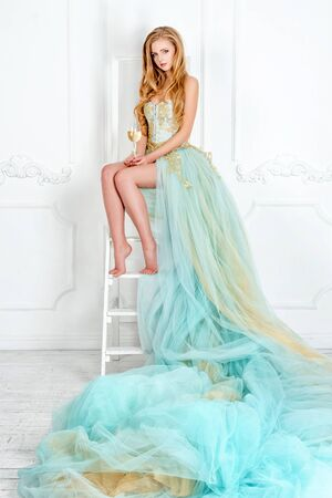Beautiful sensual blonde woman in gorgeous long dress holding glass of white wine with bottle standing on the table. Young girl celebrating. Proposing product, advertisement.