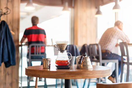 Closeup of coffee brewing gadgets on wooden table in cafe. Drip brewing, filtered coffee, or pour-over is a method which involves pouring water over roasted, ground coffee beans contained in a filter