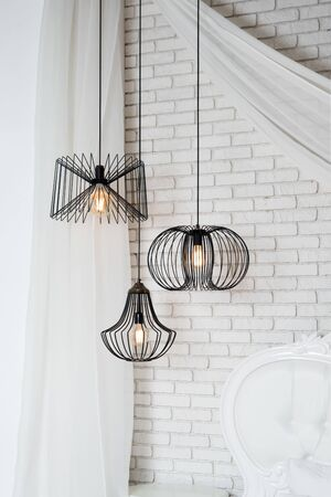 Black lamps in light bedroom interior. Three modern black lamps hanging