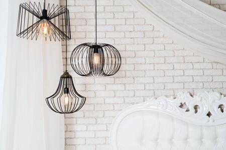 Black lamps in light bedroom interior. Three modern black lamps hanging Reklamní fotografie - 126970049