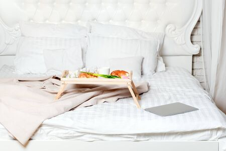 Bed with laptop and breakfast, freelancer or blogger home. Work on computer from home, morning and breakfast time Фото со стока