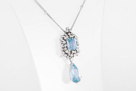 Luxury white golden pendant with blue gemstone and diamonds on stand. Фото со стока