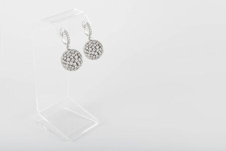 Pair of white golden diamond earrings on transparent stand. Golden earrings with diamonds, luxury jewelry Reklamní fotografie - 126483586