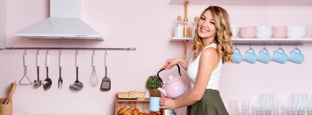 Young happy woman making coffee or tea at home in the kitchen. Blonde beautiful girl having her breakfast before going to office. Coffee break. Pink and blue pastel modern kitchen interior