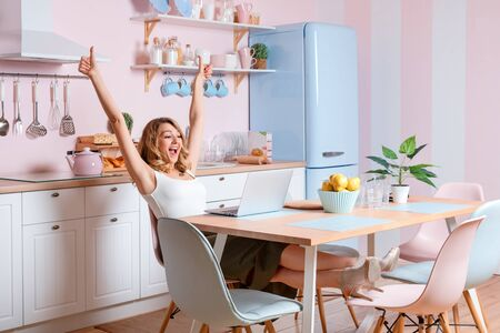 Smiling young woman using laptop in the kitchen at home. Blonde woman works on computer, freelancer or blogger working at home