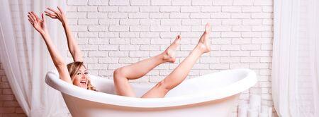 Woman in bath having fun. Beautiful young blonde woman enjoying pleasant bath, looking at camera and smiling Stock fotó