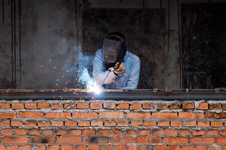 Industry worker welding iron pieces on new building