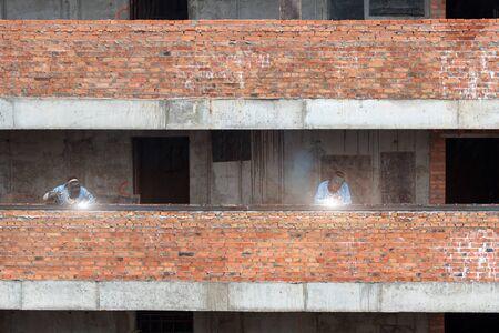 Industry workers welding iron pieces on new building Reklamní fotografie - 128705635