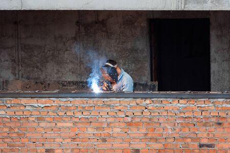 Industry worker welding iron pieces on new building Reklamní fotografie - 128705630