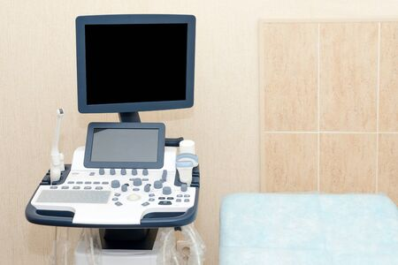 Interior of examination room with ultrasonography machine in hospital laboratory. Modern medical equipment background. Reklamní fotografie - 128705647