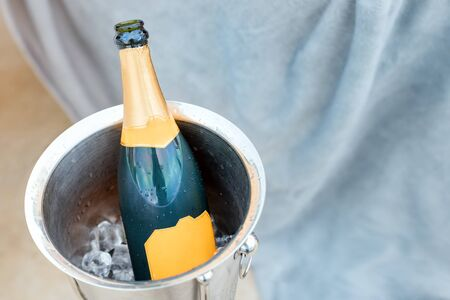 Concept of luxury life with champagne bottle in ice bucket. Celebration theme with champagne still life.