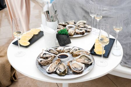 Opened oysters and lemon with white wine on the table. Restaurant delicacy, beautiful table setting. Saltwater oysters dish. Romantic dinner in restaurant.
