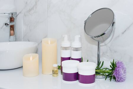 Set of natural cosmetics in beauty salon. Jars and bottles of body or hair care product on table with flowers. Space for text.