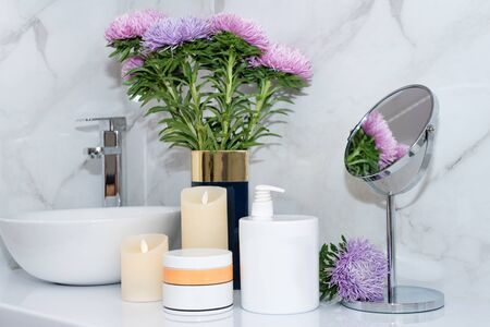 Set of natural cosmetics in beauty salon. Jars of body or hair care product on table with flowers. Space for text