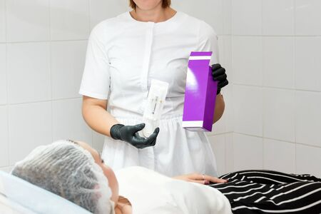 Female beautician holding cosmetic product in beauty clinic. No face. Doctor preparing patient for a cosmetic procedure