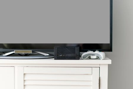 Flat LCD television on white cabinet in the living room with dark gray wall. Video gaming console and gamepad. Gamer station mockup.