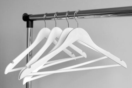 Empty clothes hangers on metal rail against grey background. Rectangular metal clothing rail with empty white wooden coat hangers Reklamní fotografie