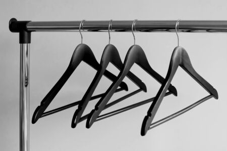 Empty clothes hangers on metal rail against grey background. Rectangular metal clothing rail with empty black wooden coat hangers