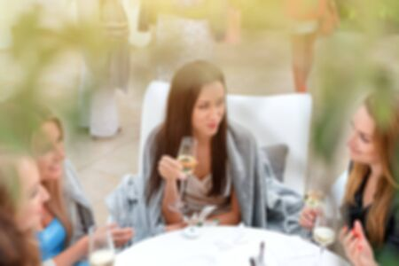 Blur portrait of smiling girls drinking wine in sunny day and talking around. Relaxed women drinking champagne in restaurant. Friends enjoying cocktails in speakeasy bar.Friendship and social concept.