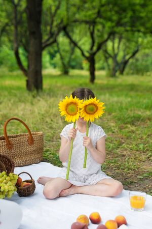 Girl holding sunflower in front of face outdoors. Outdoor party in the garden, picnic