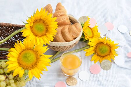 Healthy summer picnic laid out on white cloth on green grass with croissants, fresh fruit and juice. Outdoor party in the garden.