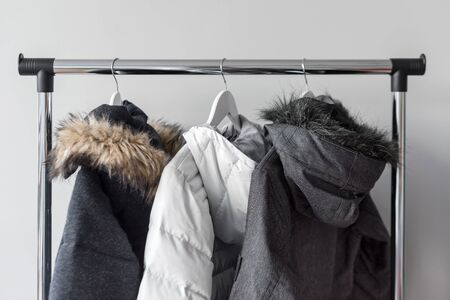 Hanger stand with warm jackets. Winter jackets with fur collar hang on white wooden hangers. Collection of winter jackets in shop. Winter season fashion background