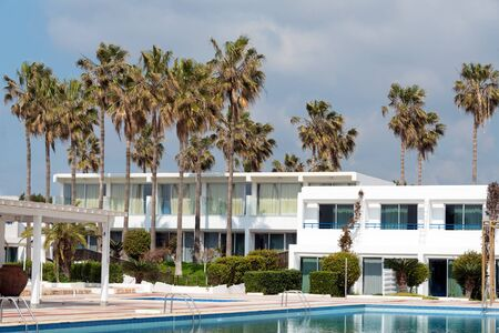 Swimming pool in luxury hotel, palm trees. 스톡 콘텐츠