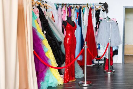 Many ladies evening gown long dresses on hanger in the dress rent shop for the wedding day or photo session. Dresses rental concept. Selective focus. Ball gown rental concept.