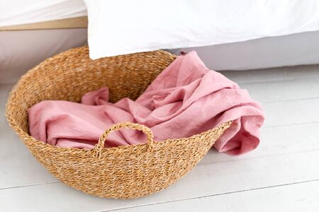 Laundry basket with pink towel. Interior of white stylish room with laundry basket